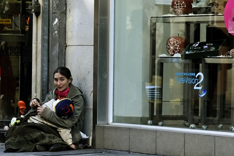 <p>A woman holds her child as she begs outside shops displaying Christmas offers in central Athens on December 9, 2011. Greece's economy remained trapped in a deep recession in the third quarter but shrank less than previously thought, at a revised 5.0 percent from an initial 5.2 percent, official figures showed today.  AFP PHOTO / LOUISA GOULIAMAKI</p>