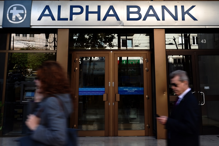 <p>People walk outside an Alpha bank branch in Athens on April 19, 2012. Greek banks have been coming under increased pressure this week as consumers have been draining their accounts.</p>