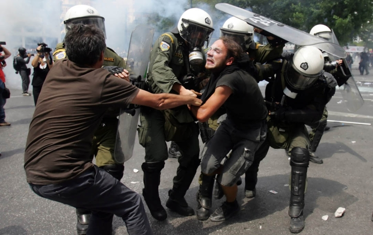 <p>Riot police arrest demonstrators as they clash with police during a protest against plans for new austerity measures on June 28, 2011 in Athens, Greece.</p>