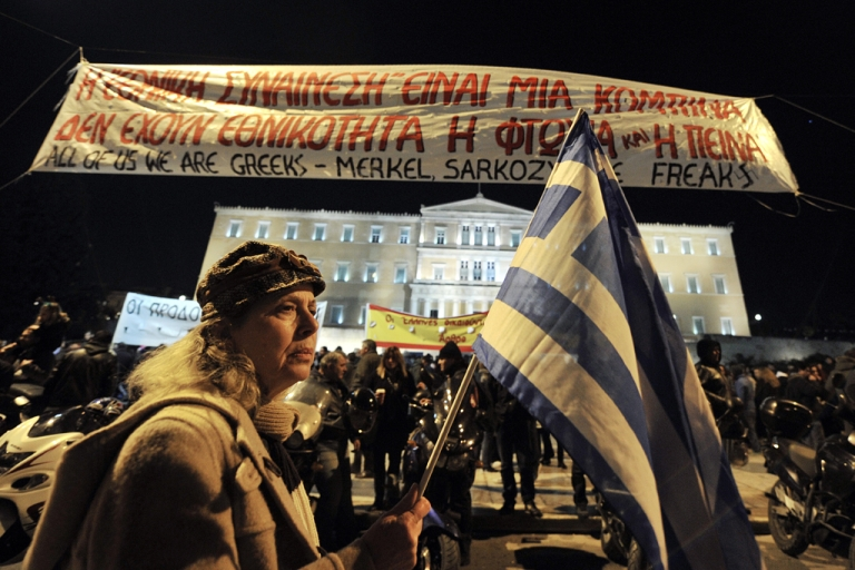 <p>A woman holds a Greek flag as she takes part in a demonstration against new austerity measures recently approved by the government, in front of the Parliament in Athens, on February 19, 2012. Greek unions and leftist parties lead fresh anti-austerity protests on the eve of a meeting of eurozone finance ministers in Brussels called to approve a $170 billion loan package needed for Athens to avoid default.</p>