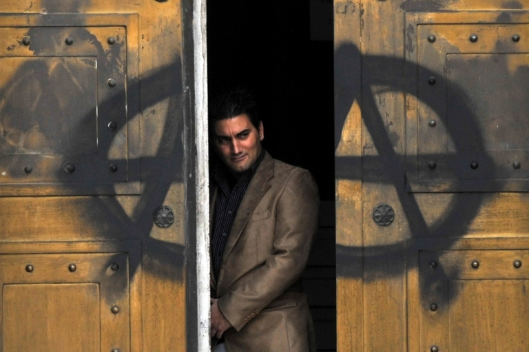 <p>A man peers from the door of the Bank of Greece marked with an A for anarchy on December 7, 2009.</p>
