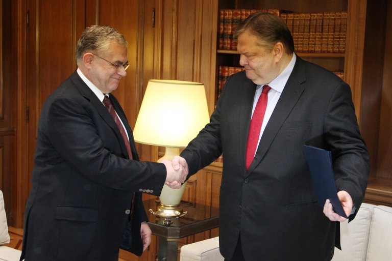<p>Greek Prime Minister Lucas Papademos (L) shakes hands with outgoing Finance Minister Evangelos Venizelos during their meeting at the Maximou Mansion in Athens, on March 19, 2012. Greek Finance Minister Evangelos Venizelos announced on Monday that he is resigning his government job after being elected on Sunday to head the Socialist party Pasok.</p>