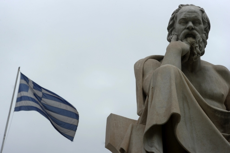<p>A Greek flag flies next to a statue of ancient Greek philosopher Socrates in the center of Athens.</p>