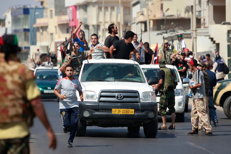 <p>Libyan rebel fighters celebrate as they drive through Tripoli's Qarqarsh district August 22, 2011.</p>