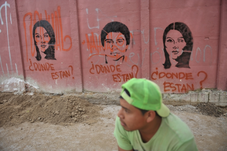 <p>A young man stands by graffiti depicting people who disappeared during the 1960-1996 civil war, during the celebration of the Army Day in Guatemala City.</p>