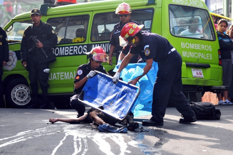<p>Firemen cover the corpse of a supposed hired assassin in Guatemala City on Sept. 1, 2010.</p>