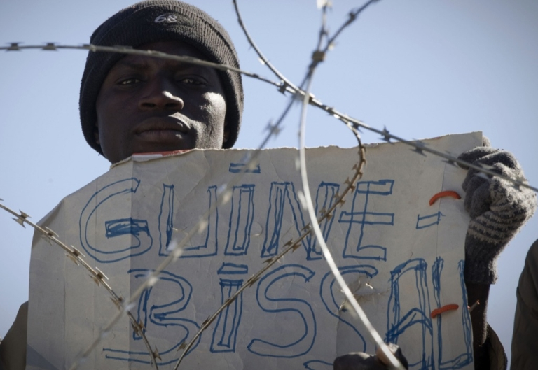 <p>As Guinea-Bissau president dies, new obstacles arise the West African state. Here, a man holds up a sign saying Guinea Bissau as he looks over barbed wire from the Libyan side of the frontier to cross at the Ras Jedir border crossing near Ben Guerdane on March 2, 2011.  The UN refugees agency made a plea today for hundreds of planes to end the gridlock at the Tunisia border with revolt-hit Libya, where