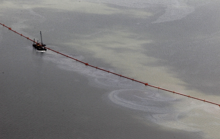 <p>The sheen last time: an oil sheen and boom are seen in July, 2010 in Grand Isle, Louisiana. Ships and rig workers were evacuating the oil spill area as Tropical Storm Bonnie approached the region.</p>