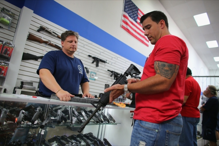 <p>Jonathan Schwartz, a salesman at the National Armory gun store, helps Reese Magnant as he looks to buy a National Armory AR-15 Battle Entry Assault Rifle on January 16, 2013 in Pompano Beach, Florida.</p>