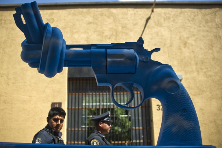 <p>Mexican policemen walk by a sculpture of a knotted gun in Mexico City.</p>