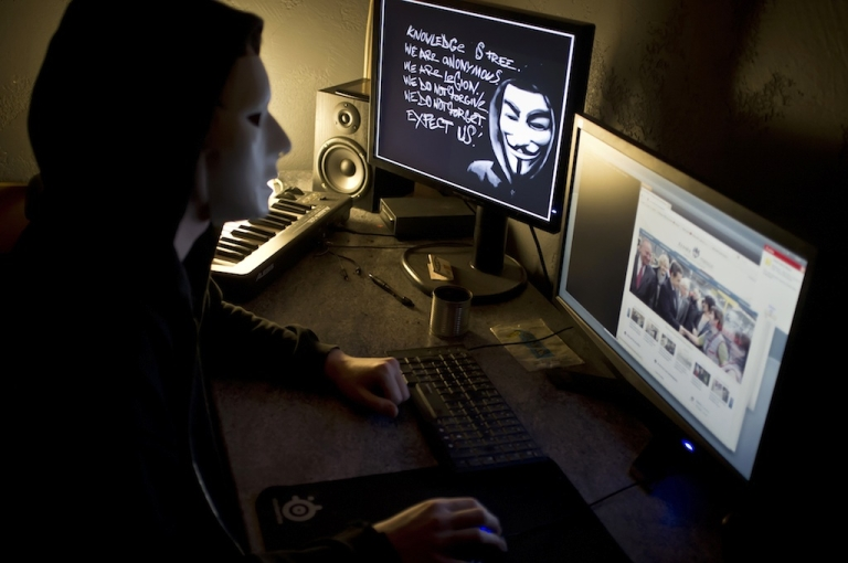 <p>A masked hacker, who belongs to the Anonymous group, hacks the French presidential Elysee Palace website on January 20, 2012 near the eastern city of Lyon.</p>