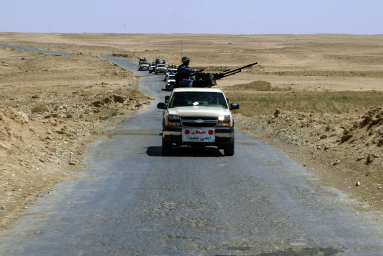<p>Iraqi police officers patrol a main road leading out of the town of Haditha, 260 km north-west of Baghdad.</p>