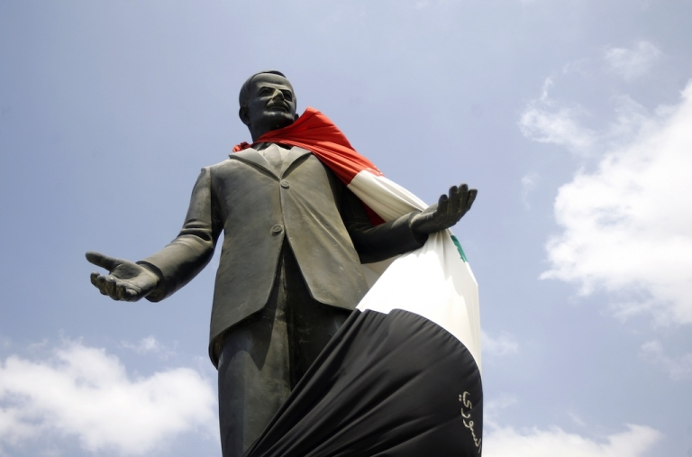 <p>A Syrian flag hangs over a statue of the late president Hafez al-Assad on Aug. 30, 2011, near Homs. Alawites have ruled Syria since Hafez seized power in 1970.</p>