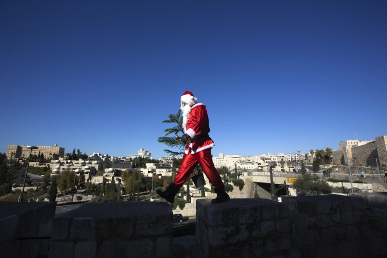 <p>A Palestinian man dressed up as Santa Claus carries a Christmas tree and rings a bell as he walks along the wall of Jerusalem's Old City, on December 23 2012, as Christians around the world prepare for Christmas celebrations.</p>
