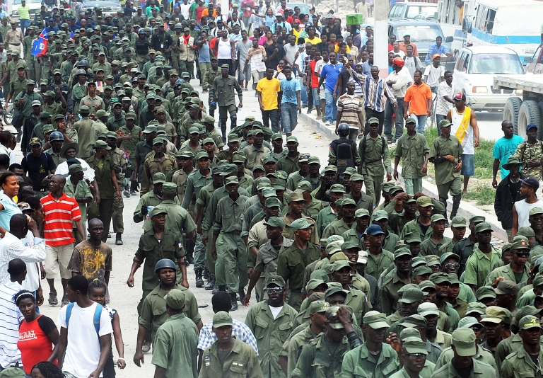 <p>Former Haitian soldiers march during a May 18, 2012, protest near the UN peacekeeping post in the Carrefour neighborhood of Port-au-Prince.</p>