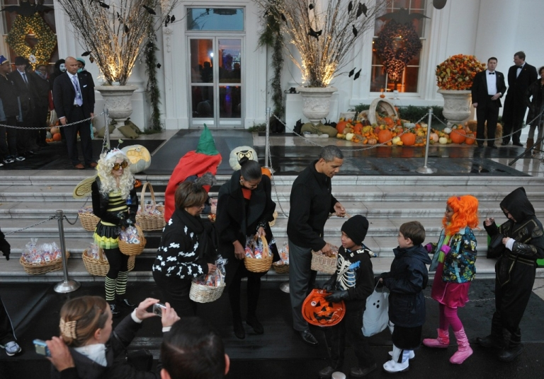 <p>Barack and Michelle Obama welcome trick-or-treaters at the White House. That's candy, not bibles, in the baskets.</p>