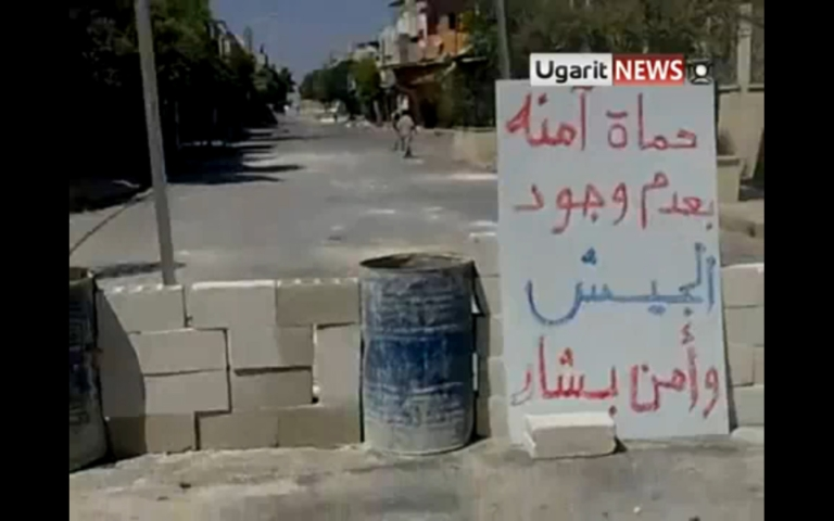 """<p>A make-shift roadblock set up by residents of Hama in an effort to prevent the return of the army and security forces. The sign reads: """"Hama is safe without the presence of Bashar's army or security forces.""""</p>"""