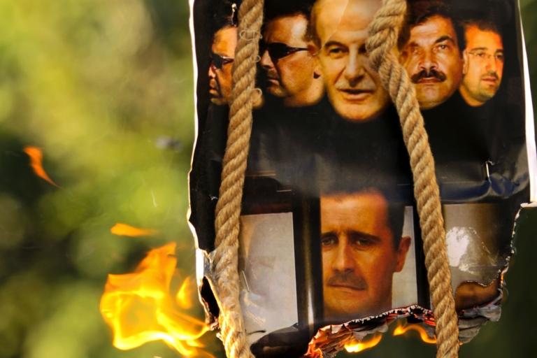 <p>A makeshift gallows with a poster shows the pictures of former Syrian president Hafez al-Assd (top-C), his sons current President Bashar al-Assad (2nd L and bottom C) and Maher (L), their brother in-law General Assef Shawkat (2nd R) and businessman Rami Makhluf (R), during an anti-regime protest outside the Syrian embassy in the Cypriot capital Nicosia on July 31, 2011.</p>