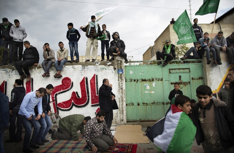 <p>Palestinians pray as others watch on during a rally to mark the 25th anniversary of Hamas in Gaza City on December 8, 2012.</p>