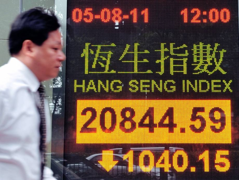 <p>A man walks past a display board showing the Hang Seng Index in Hong Kong on August 5, 2011. Hong Kong shares dived more than five percent amid a worldwide sell-off.</p>