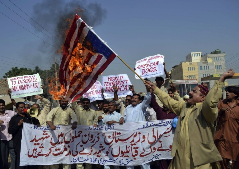 <p>A Pakistani protester holds a burning US flag as others shout slogans during a protest in Multan on October 31, 2011 against US drone attacks in the Pakistani tribal region. Relations between Pakistan and the United States deteriorated after the May 2, 2011 killing of Al Qaeda leader Osama bin Laden by US Navy SEALs in Abbottabad, Pakistan, and again over accusations that Pakistani intelligence was involved with the Haqqani network.</p>