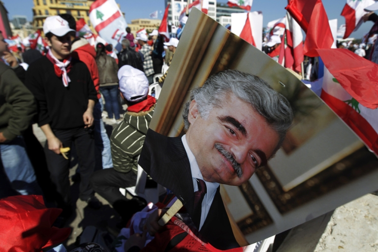 <p>A man holds a picture of Lebanese slain Prime minister Rafic Hariri as he takes part in a mass rally gathering tens of thousands opposition supporters marking the sixth anniversary of a popular uprising against Syrian troops in Lebanon, demanding the disarming of Hezbollah, on March 13, 2011 in central Beirut.     AFP PHOTO / JOSEPH EID (Photo credit should read JOSEPH EID/AFP/Getty Images)</p>