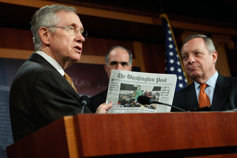 <p>Senate Majority Leader Harry Reid (L) holds up a copy of today's Washington Post during a news conference about extending the payroll tax cut with US Sen. Robert Casey and Senate Majority Whip Richard Durbin at the US Capitol on Dec. 7, 2011.</p>