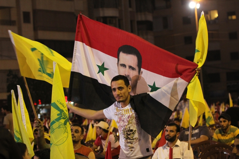 <p>Lebanese Hezbollah supporters wave the movement's yellow flags and hold up the Syrian flag decorated with an image of President Bashar al-Assad as they listen to a televised speech by Hezbollah chief Hassan Nasrallah to mark the sixth anniversary of the 2006 war with Israel in southern Beirut on July 18, 2012.</p>