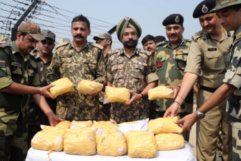 <p>Indian Border Security Force (BSF) Additional Director General (ADG) Himmat Singh (C), BSF Deputy Inspector General (DIG) Sanjeev Bhanot (3R) BSF 41 Battalion Commandant Ish Aul (2L) along with BSF personnel pose with 27 kilogrammes of confiscated heroin during a press conference held close to The India-Pakistan Border at Rajatal, some 40kms from Amritsar on October 6, 2011.  Singh said that BSF personnel recovered the drugs after an encounter with alleged miscreants close to the border between the South Asian neighbours a haul of nine bundles of narcotics with each containing 3 packets,  total 27 packets . The narcotics were allegedly smuggled into the country from neighbouring Pakistan, officials said.</p>
