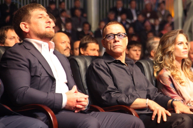 <p>Belgian actor Jean-Claude Van Damme (C) looks at Chechen leader Ramzan Kadyrov (R) as they watch, with Hilary Swank (R), a performance in Grozny late on October 5, 2011.</p>