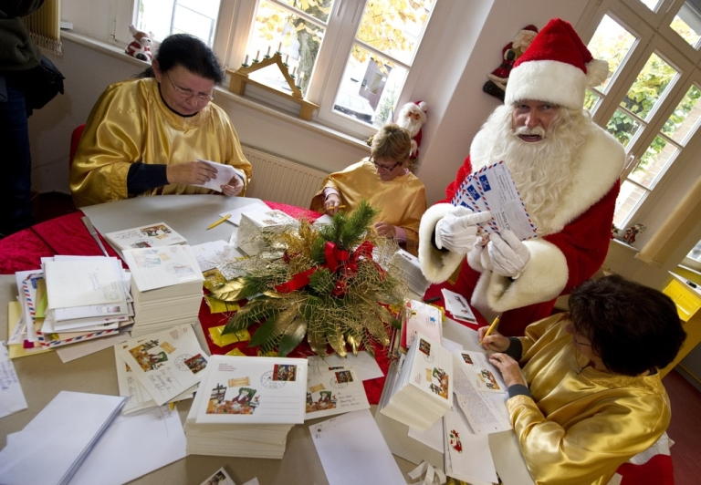 <p>A man dressed as Santa Claus poses with his 'helpers' who are busy answering children's letters in the Santa Claus post office in the Eastern German town of Himmelpfort (Heaven's Gate) on November 10, 2011. Children can send their Christmas wish lists to Himmelpfort from around the world and receive a reply from Santa. In 2010, the post office here received 285.000 letters in 17 languages.</p>