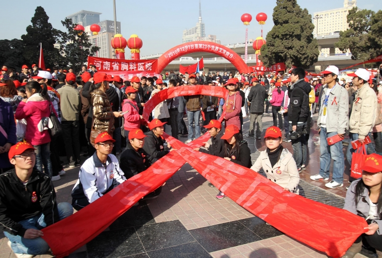 <p>AIDS activists gather to form a red ribbon, marking the World's AIDS day in Zhengzhou, central China's Henan province on December 1, 2010. A retired senior Chinese health official Chen Bingzhong, 78, who has advanced liver cancer, called for two of the country's most powerful leaders to take responsibility for a huge 1990s blood-selling AIDS scandal in Henan province. CHINA OUT AFP PHOTO</p>