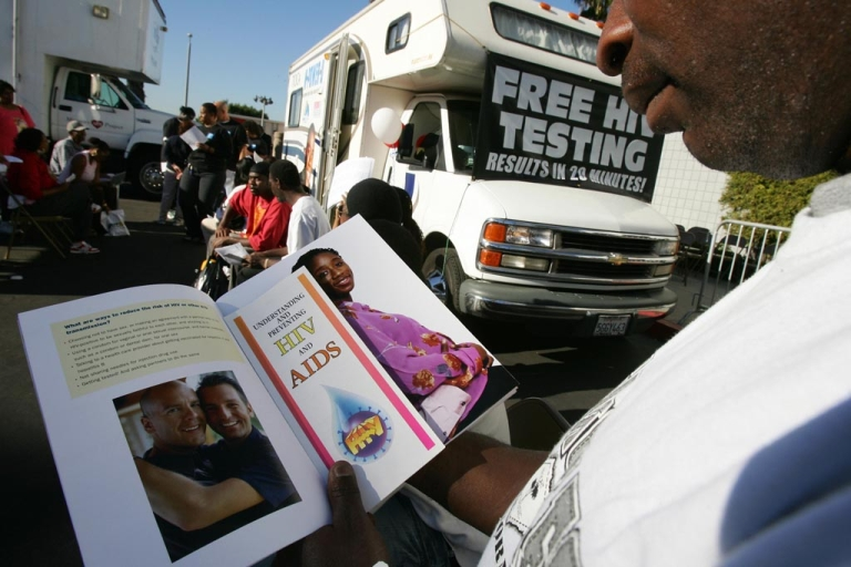 <p>A man reads education literature as he waits for an HIV test at a free mobile testing center in Los Angeles.</p>