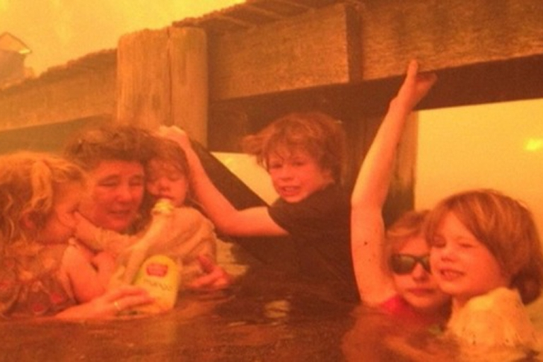 <p>Tammy Holmes and her grandchildren cling to a boat jetty to escape the flames of a wildfire in Tasmania.</p>