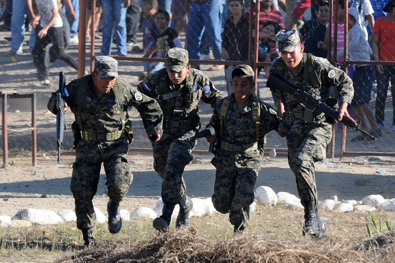 <p>Need a hand? Honduran military seen attending to a recent prison fire. The country's military struggles to stamp out narco trafficking. Now they are carrying out joint operations with US Special Forces to chase down drug runners.</p>