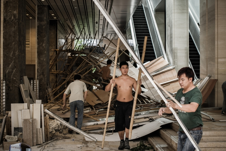 <p>Workers clean debris from a collapsed scafolding in the aftermath of Typhoon Vincente in Hong Kong on July 24, 2012.</p>