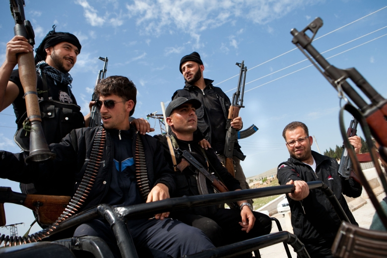 <p>Syrian fighters hold their weapons at a checkpoint controlled by the Free Syrian Army. The Syrian government claimed that 25 citizens were massacred by
