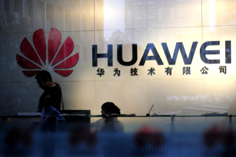 <p>Staff and visitors walk pass the lobby at the Huawei office in Wuhan in central China's Hubei province on Oct. 8, 2012.</p>