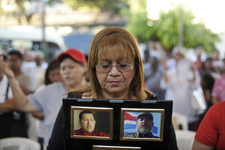 <p>A woman holds pictures of Venezuelan President Hugo Chavez and former Cuban President Fidel Castro during a ceremony in support of Chavez's health, on Jan. 10, 2013 at the Simon Bolivar Park in El Salvador.</p>