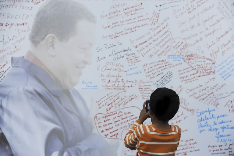 <p>A boy takes pictures of a poster with the image of Venezuelan President Hugo Chavez in Caracas.</p>