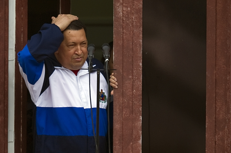 <p>Venezuelan President Hugo Chávez greets supporters from the Miraflores presidential palace in Caracas on April 13.</p>