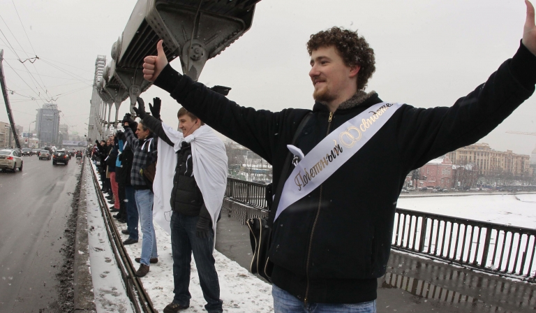 <p>Russian opposition supporters, holding white ribbons, form a chain around Moscow on February 26. A din of endless honking descended on the capital's 16-kilometer Garden Ring road as drivers expressed support for the protesters.</p>