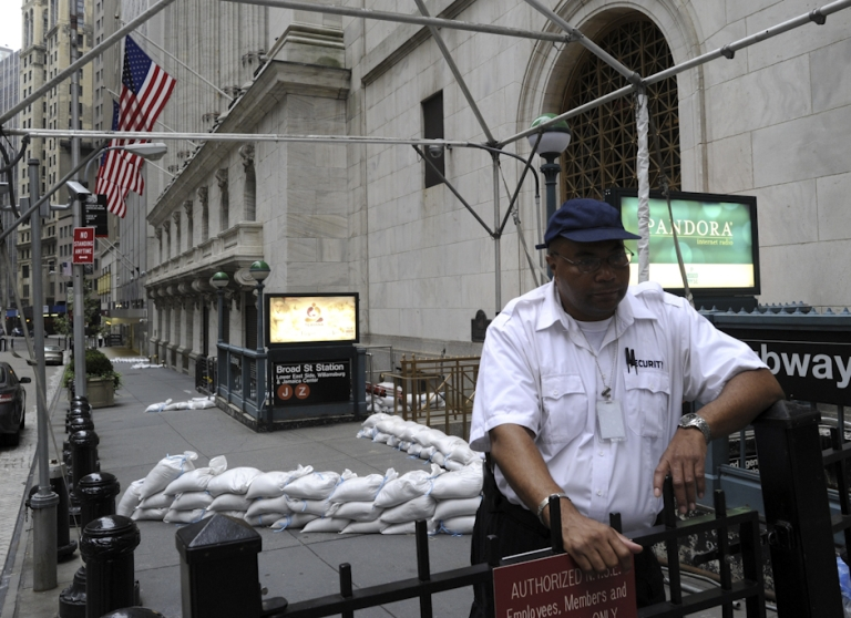 <p>A security guard near the sand bagged front entrance of the New York Stock Exchange August 27, 2011. Hurricane Irene hit New York City on Sunday morning, but despite the strong winds, torrential rains and threat of flooding, the NYSE and Nasdaq both said they expect to be open for trading as usual on Monday morning.</p>