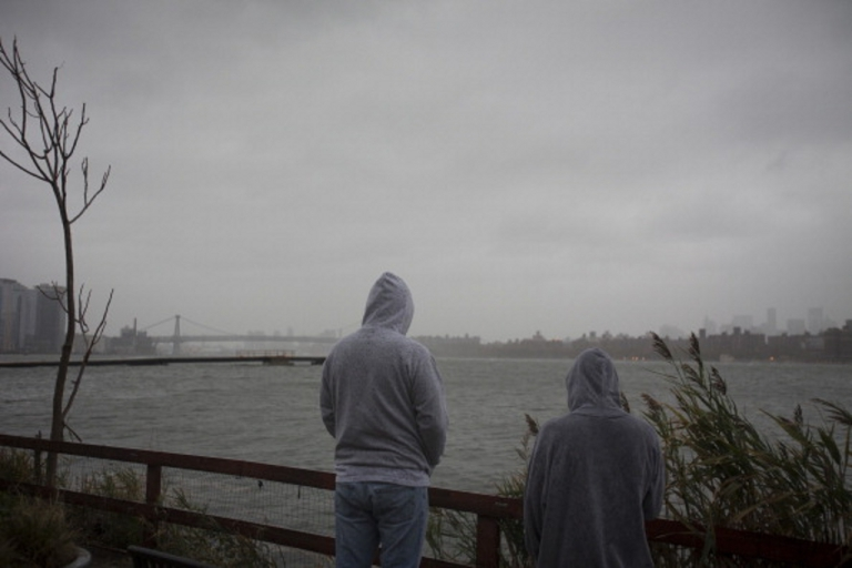 <p>Onlookers watch as the storm gathers over Manhattan in New York, U.S., on Monday, Oct. 29, 2012. Hurricane Sandy strengthened on its path toward New Jersey, where it is predicted to make landfall today while bringing a life-threatening storm surge as it whips a region of 60 million people with high winds and rain.</p>