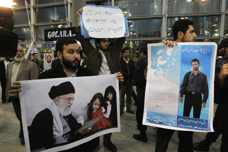 <p>Iranian students hold a poster of assassinated nuclear scientist Mostafa Ahmadi-Roshan (R) and a picture of the family of killed nuclear scientist Dariush Rezaei with Iran's supreme leader Ayatollah Ali Khamenei as they protest at the Imam Khomeini airport in Tehran on January 29, 2012 during the arrival of the International Atomic Energy Agency (IAEA) inspectors.</p>