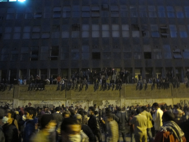 <p>People sitting on the American University in Cairo's wall watching the fight between protesters and Central Security Forces at Mohamed Mahmoud Street.</p>