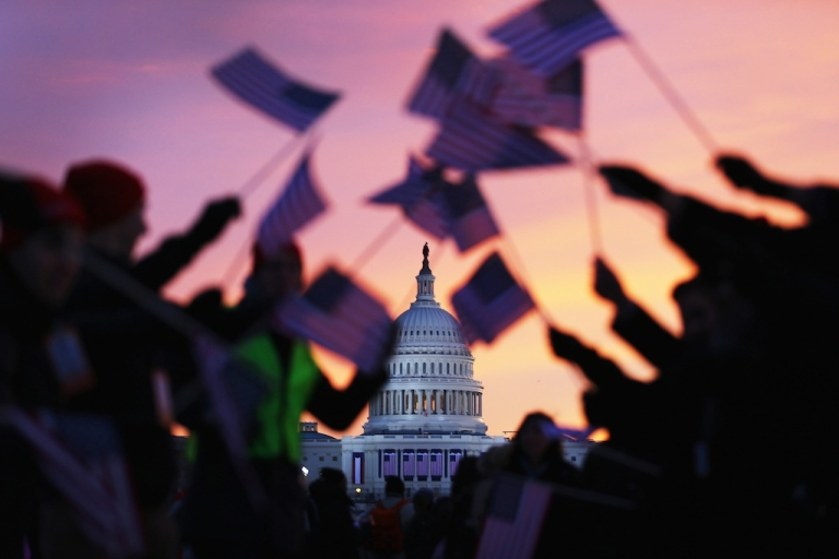 <p>People wave American flags near the Capitol building on the National Mall on Jan. 21, 2013 in Washington, DC.</p>
