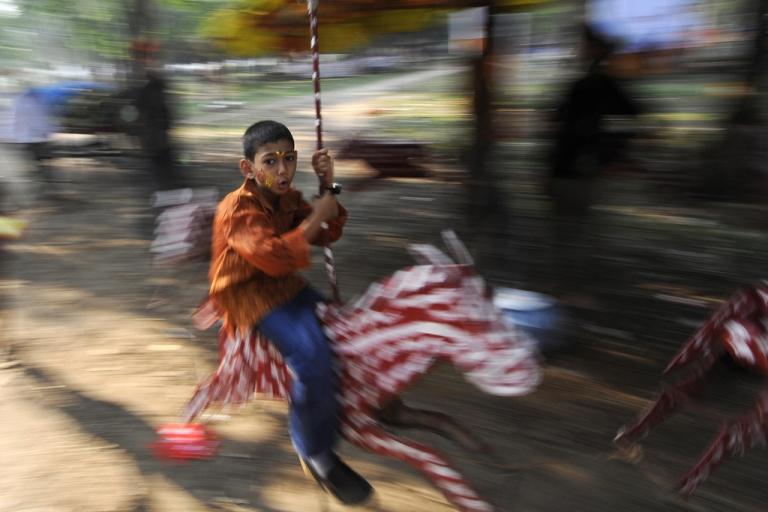 <p>A Bangladeshi child rides on a merry-go-round.</p>