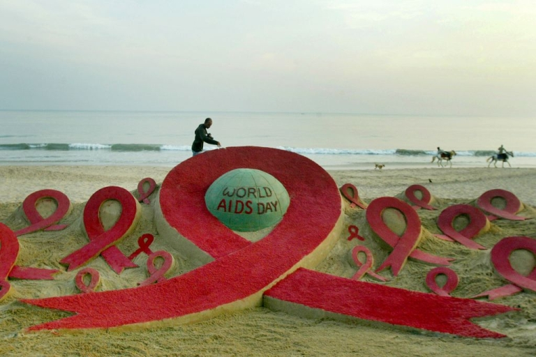 <p>Horses canter past an AIDS-awareness sand sculpture on Golden Sea beach in Puri, India.</p>