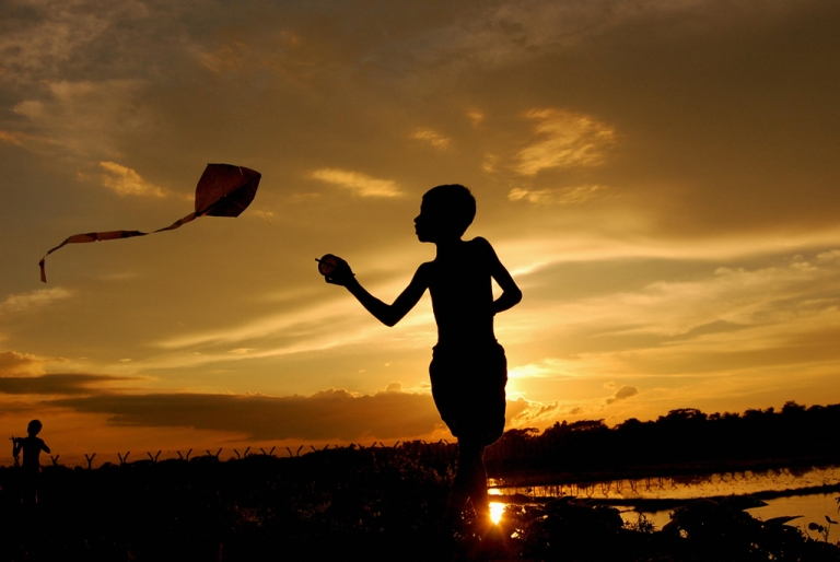 <p>An Indian boy flies a kite against the backdrop of a sunset near the Indo-Bangladesh border village Raimura near Agartala, capital of Indian northeastern state Tripura on July 26, 2008.</p>